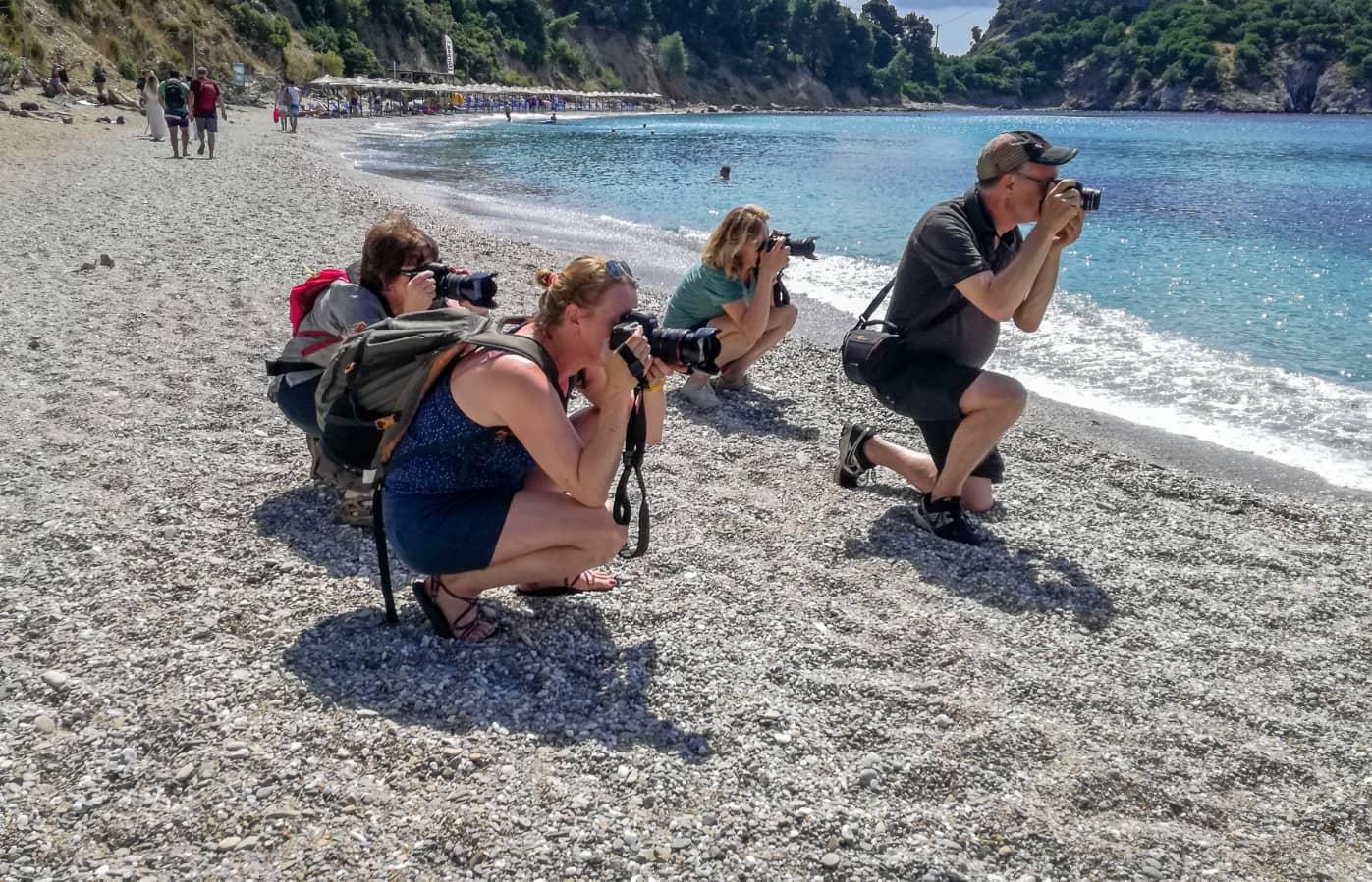 fotografen op Skopeloos, Griekenland op het strand bij de kustlijn