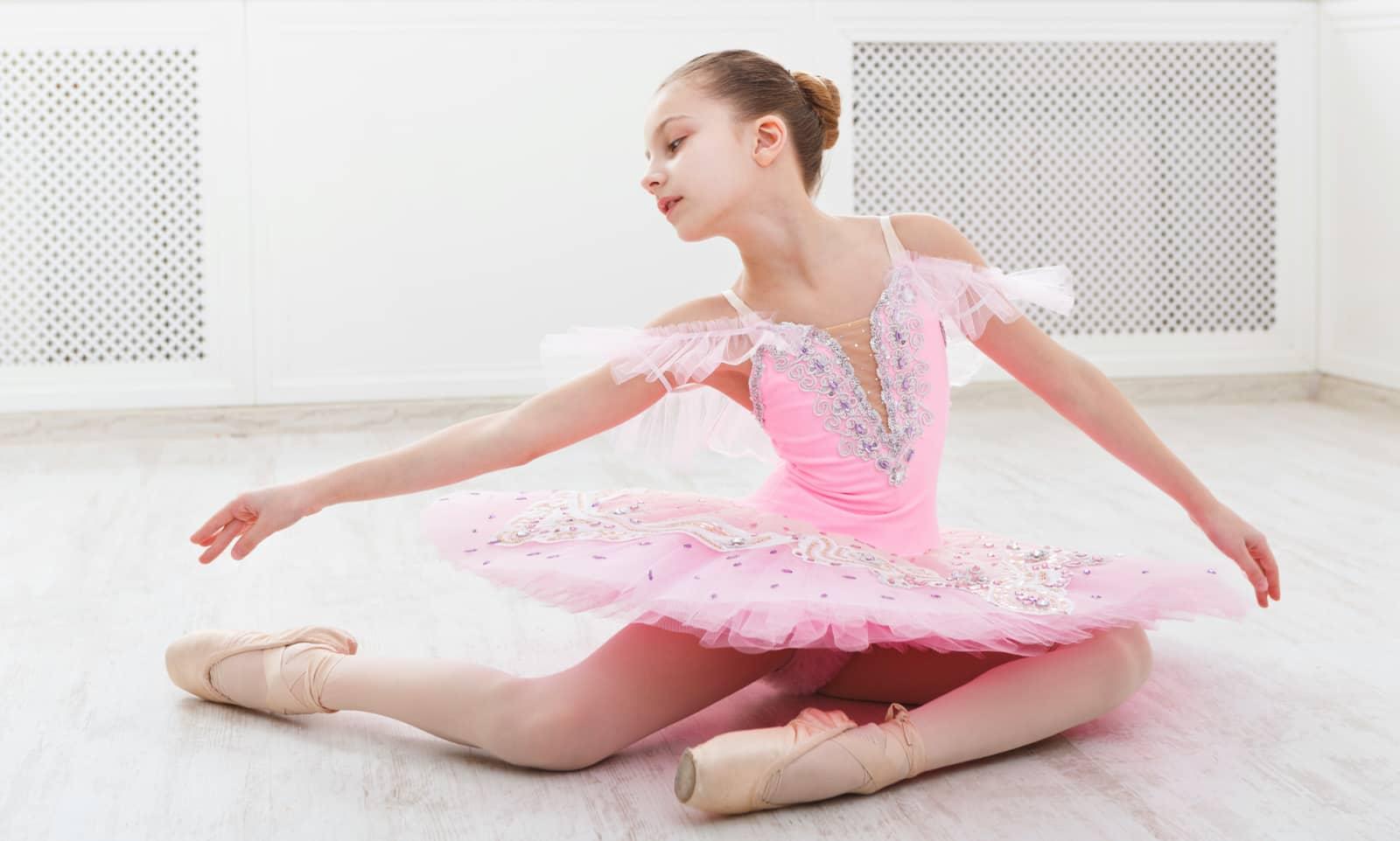 Jong meisje in roze balletpakje op grond in ballethouding