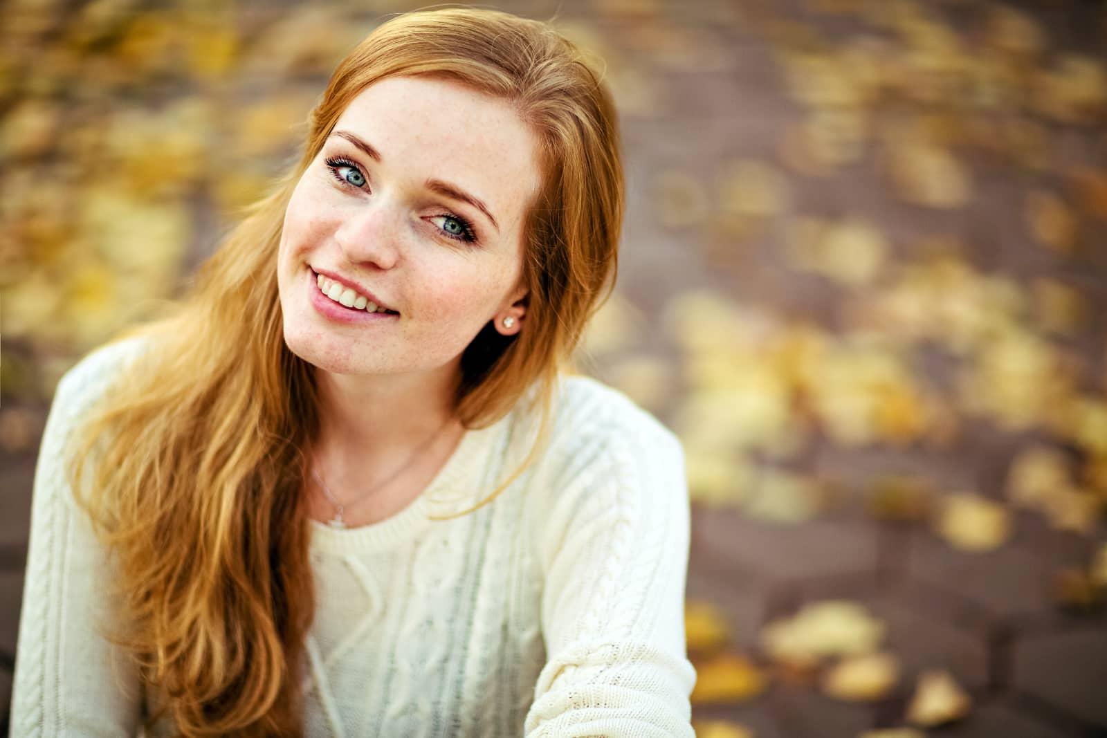 vrouw met rood haar lachend met vage herfstachtergrond