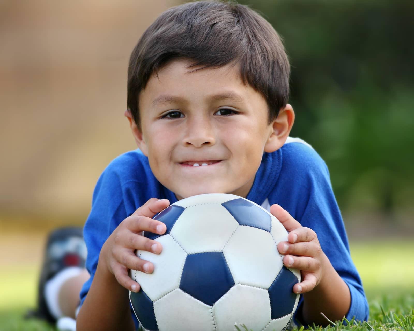 jongen liggend op buik met voetbal onder kin