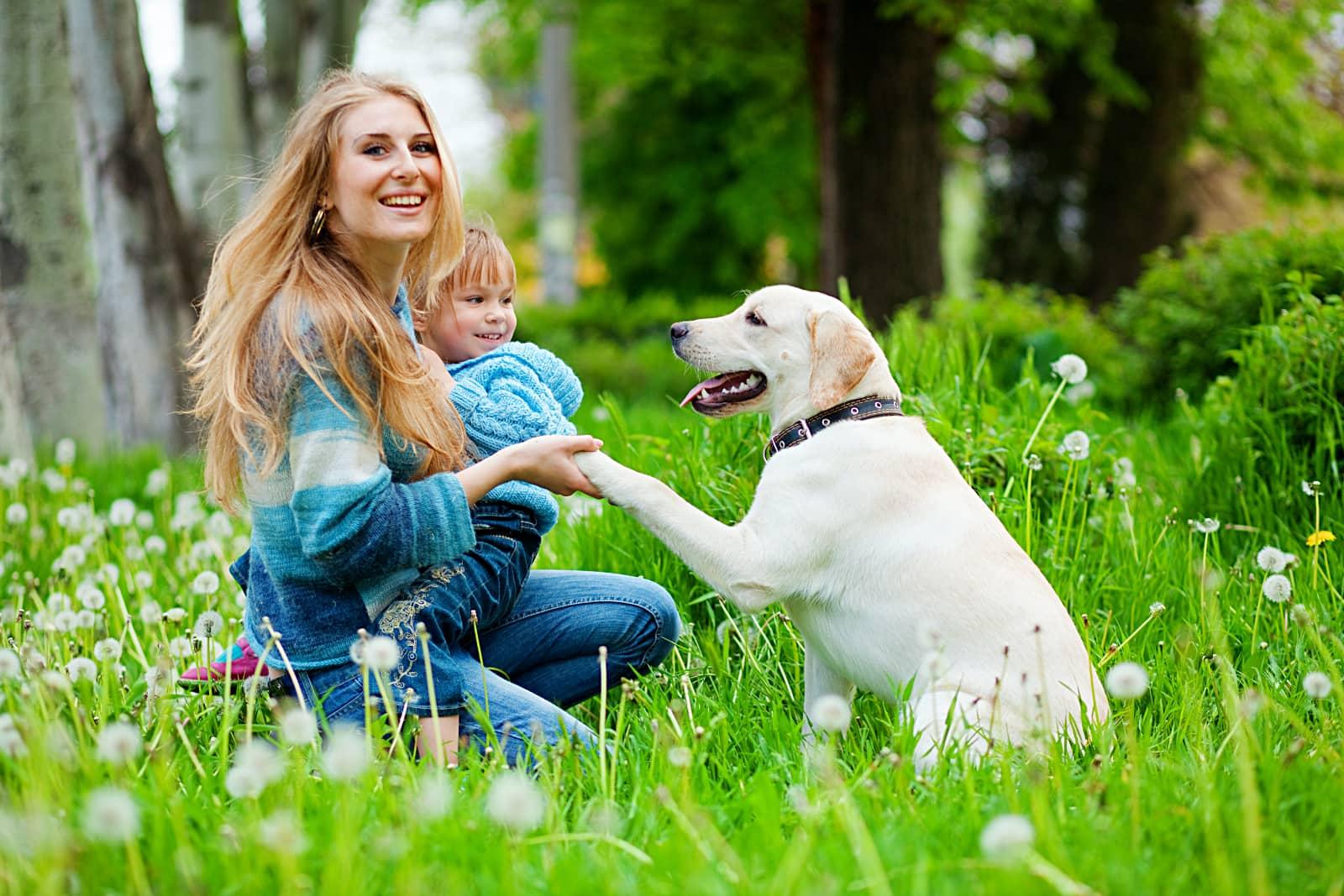 vrouw met kind op schoot geeft poot aan witte hond in bos