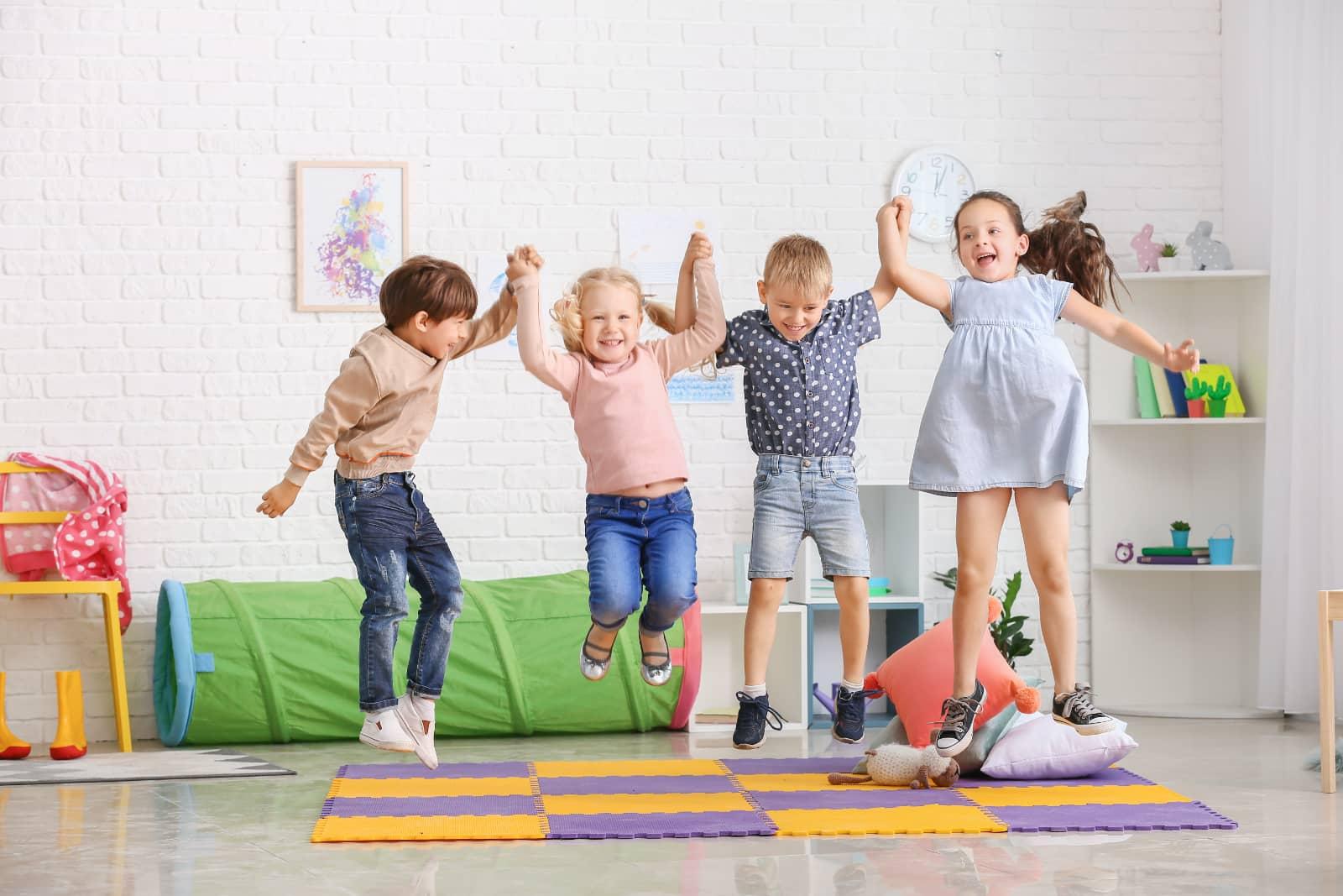 kinderen in kinderdagverblijf springen hand in hand