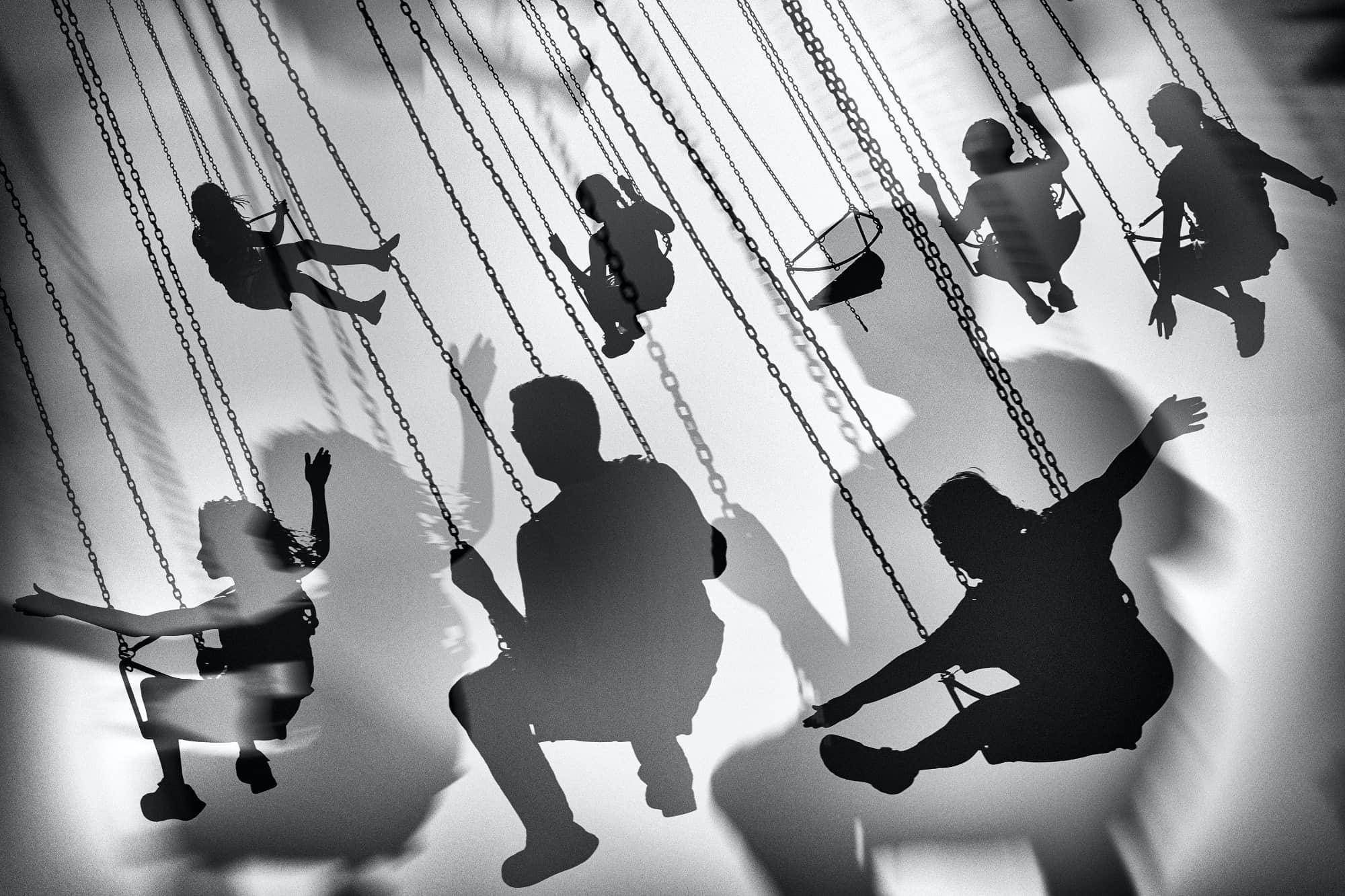 zwart wit mensen op schommels van draaimolen- fotograaf Jacek Patora, Poland, National Awards, 2020