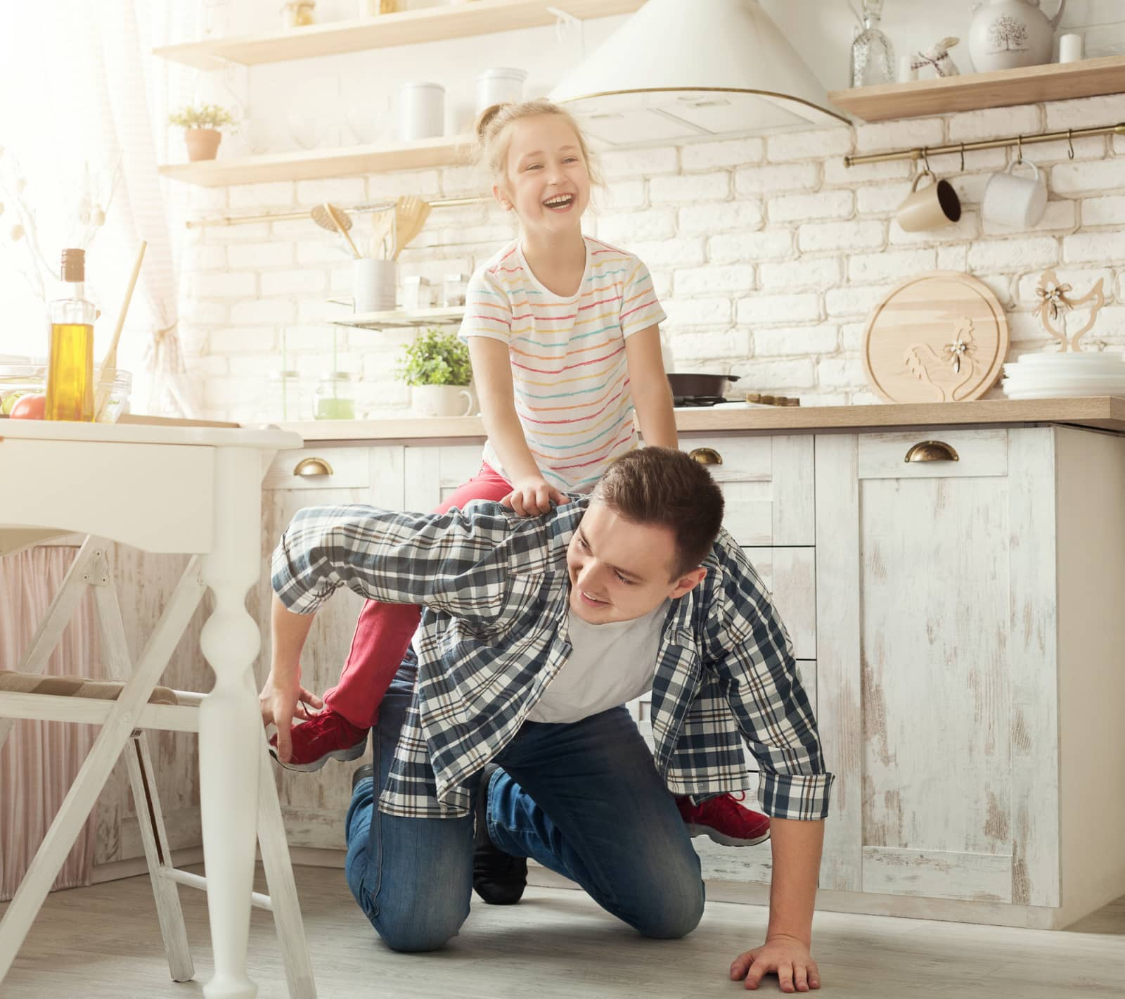 papa rijdt paarje met dochter in keuken