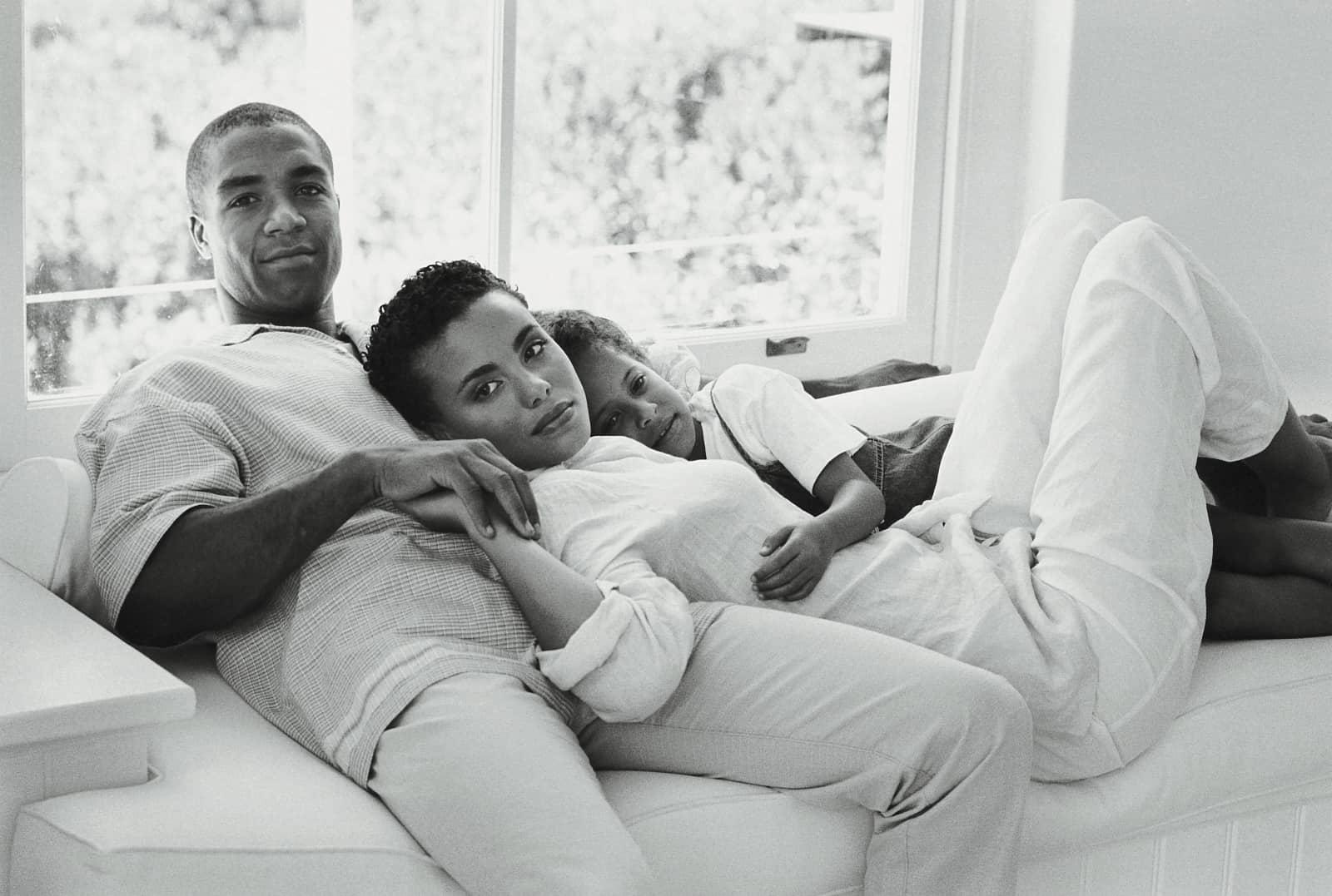 man vrouw en kind liggen op bank, zwartwit