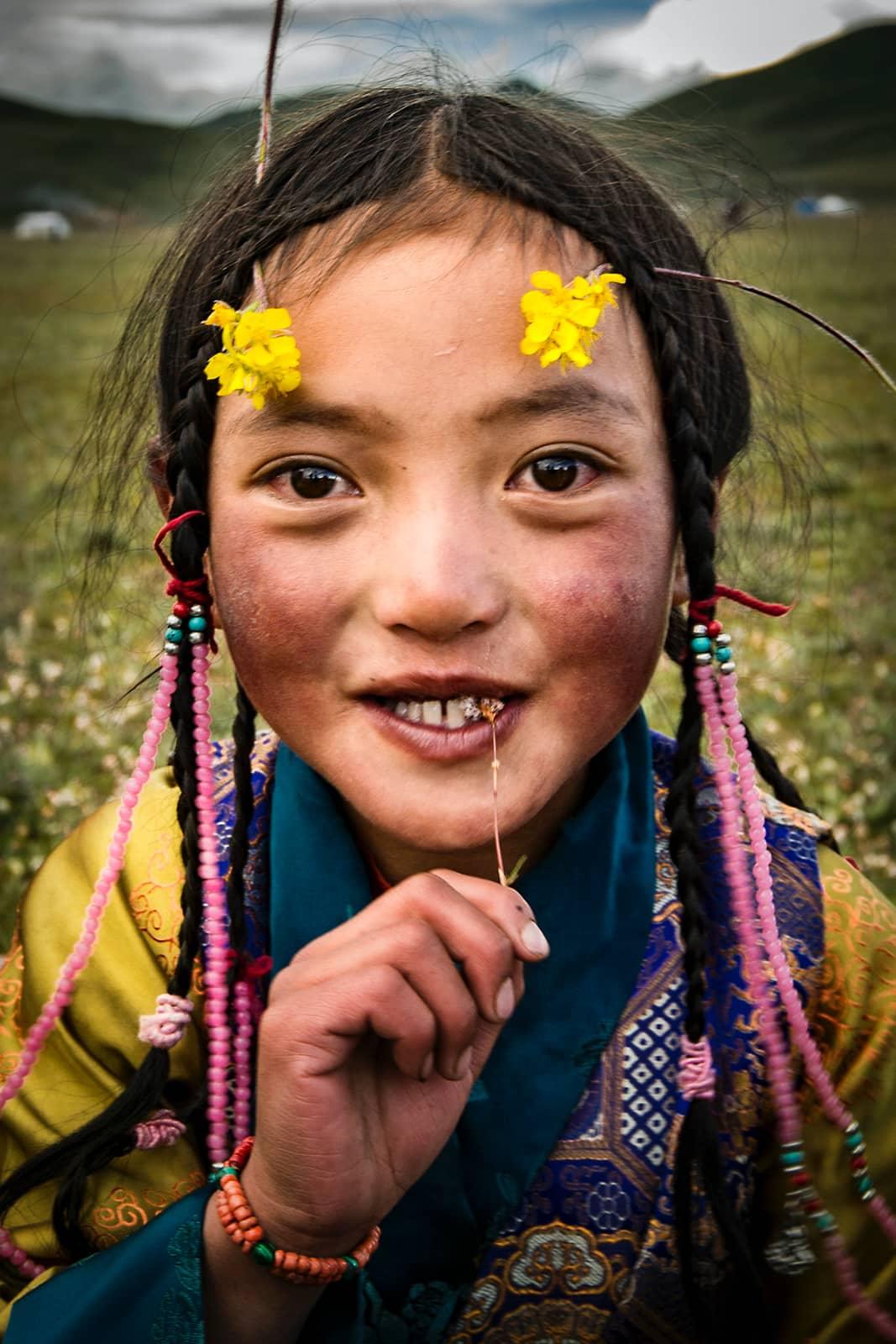 Portret van eskimo meisje met bloemetjes en vlechtje in haar in gebied met heuvels en wolken, Photographer: Zijie Gong, China