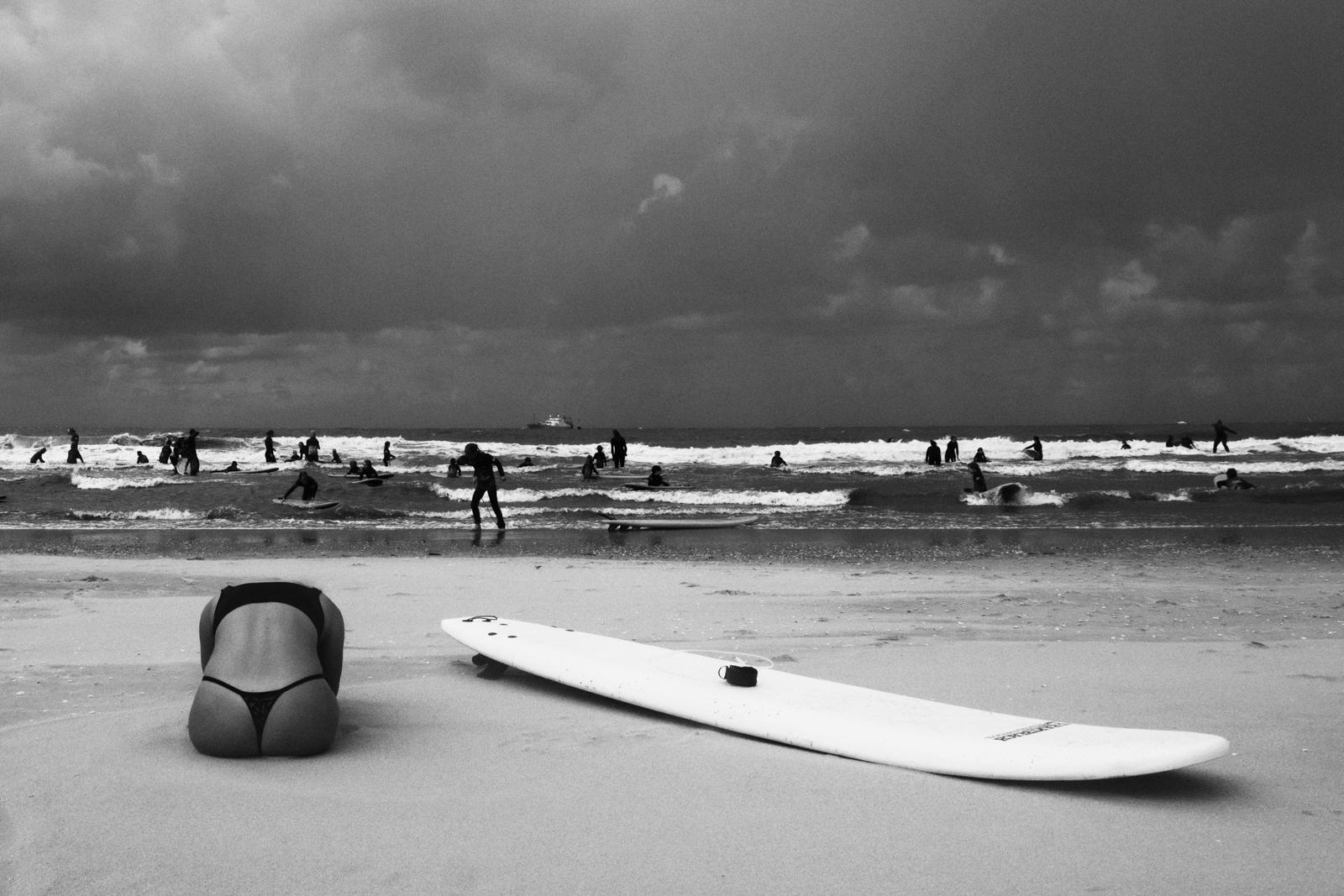 Foto van Merel Schoneveld van strand in zart wit met mensen in branding en op zand ligt surfboard en een vrouw in yoga houding