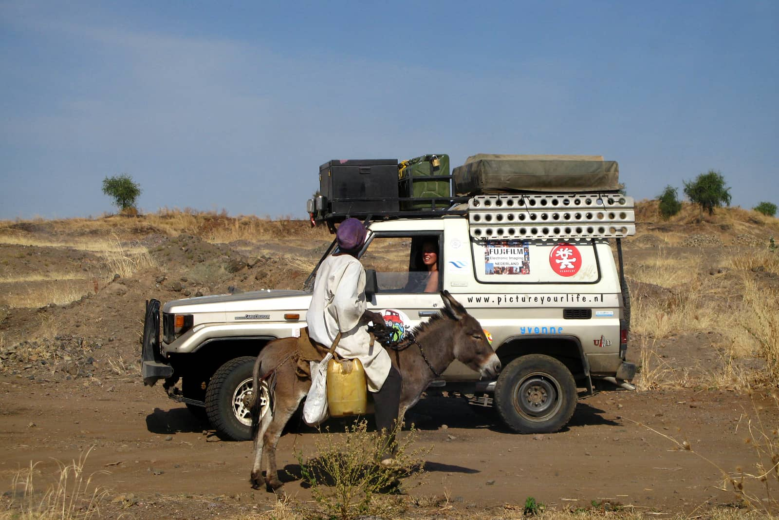 Ilvy Njiokiktjien in jeep in woestijn Sudan pratend tegen man op ezel