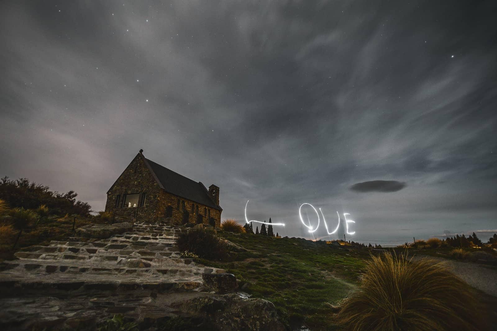 Lightpainting huis op heuvel met tekst Love in de lucht