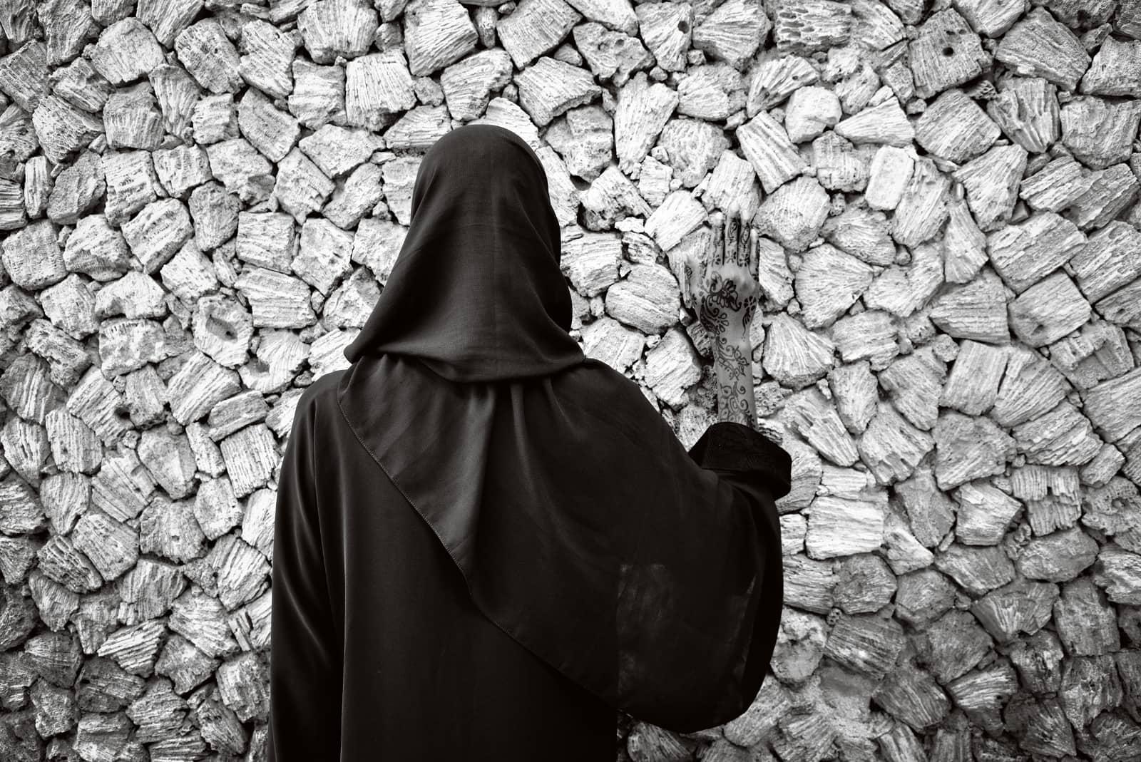 © Annelies Damen - Fikra, vrouw in zwart gekleed met zwart hoofddoek staat met rug naar camera tegen een muur met hand op muur