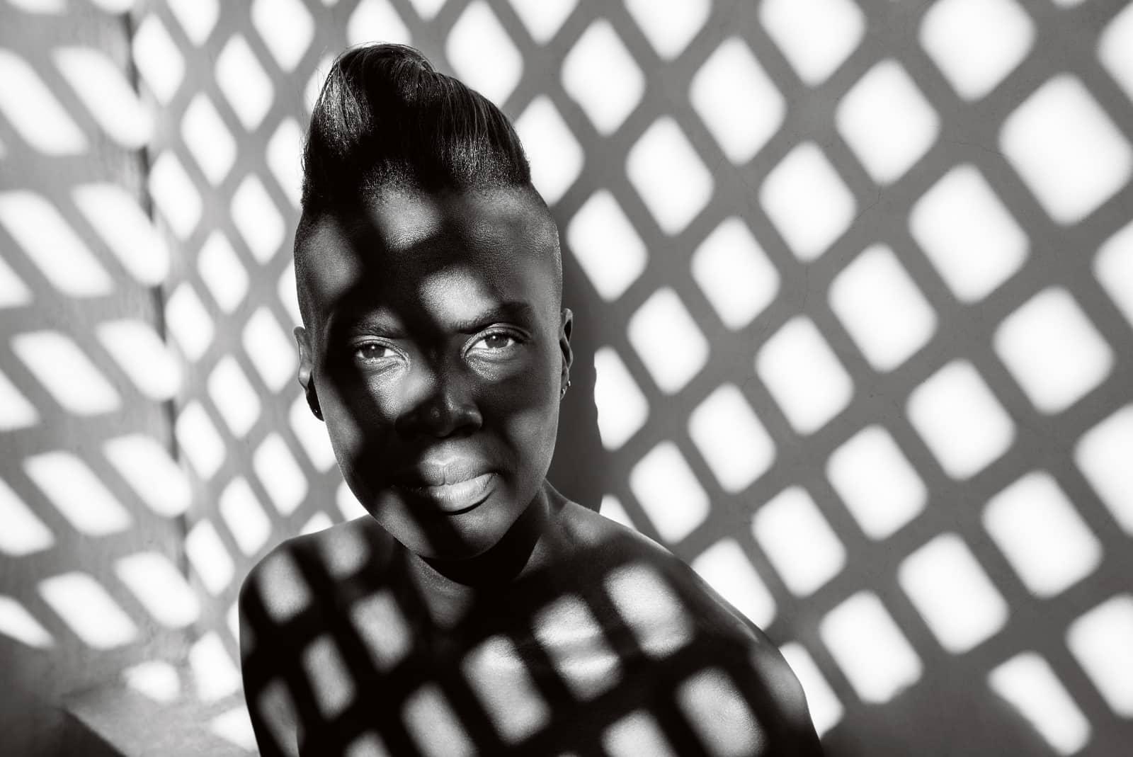 © Annelies Damen - Angalia: portret zwarte vrouw met licht dat door een hekwerk valt