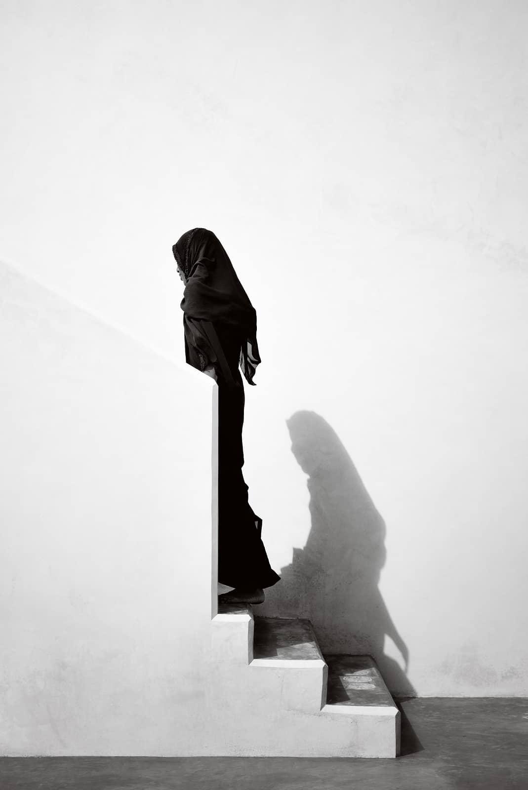 © Annelies Damen - Adabu, vrouw in zwart gekleed met hoofddoek loopt trap op