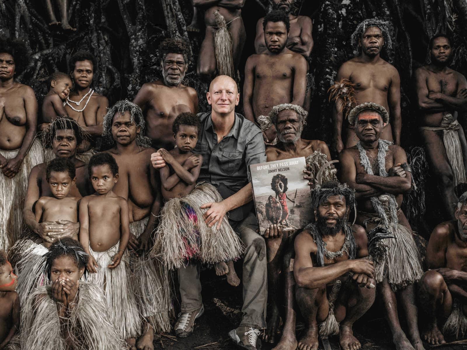 foto: © Jimmy Nelson - Before They Pass Away - Jimmy temidden van groep van inheems volk waarbij zijn boek wordt vastgehouden