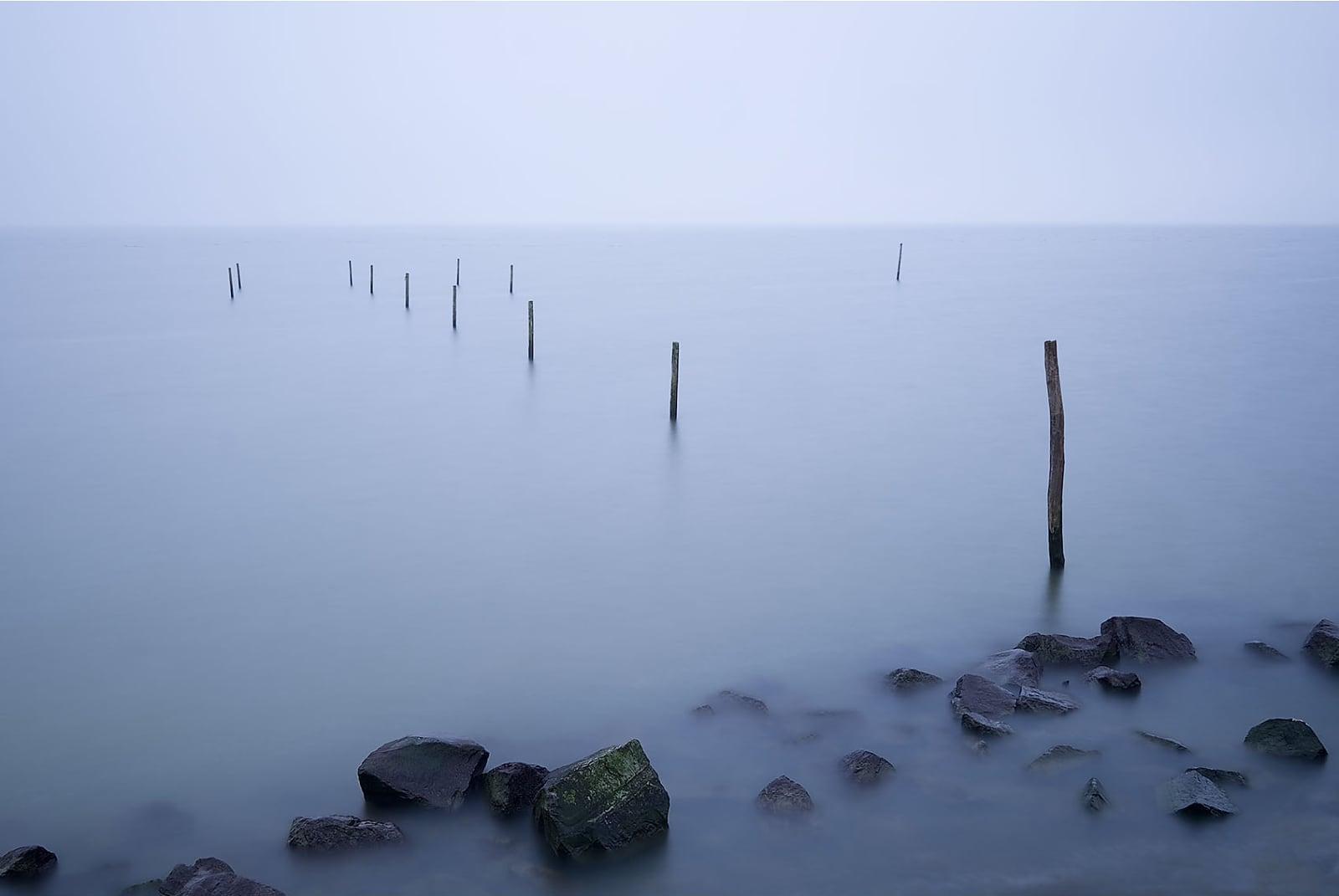 foto: © Jan Duker - Kust en Zee, palen in mistige zee