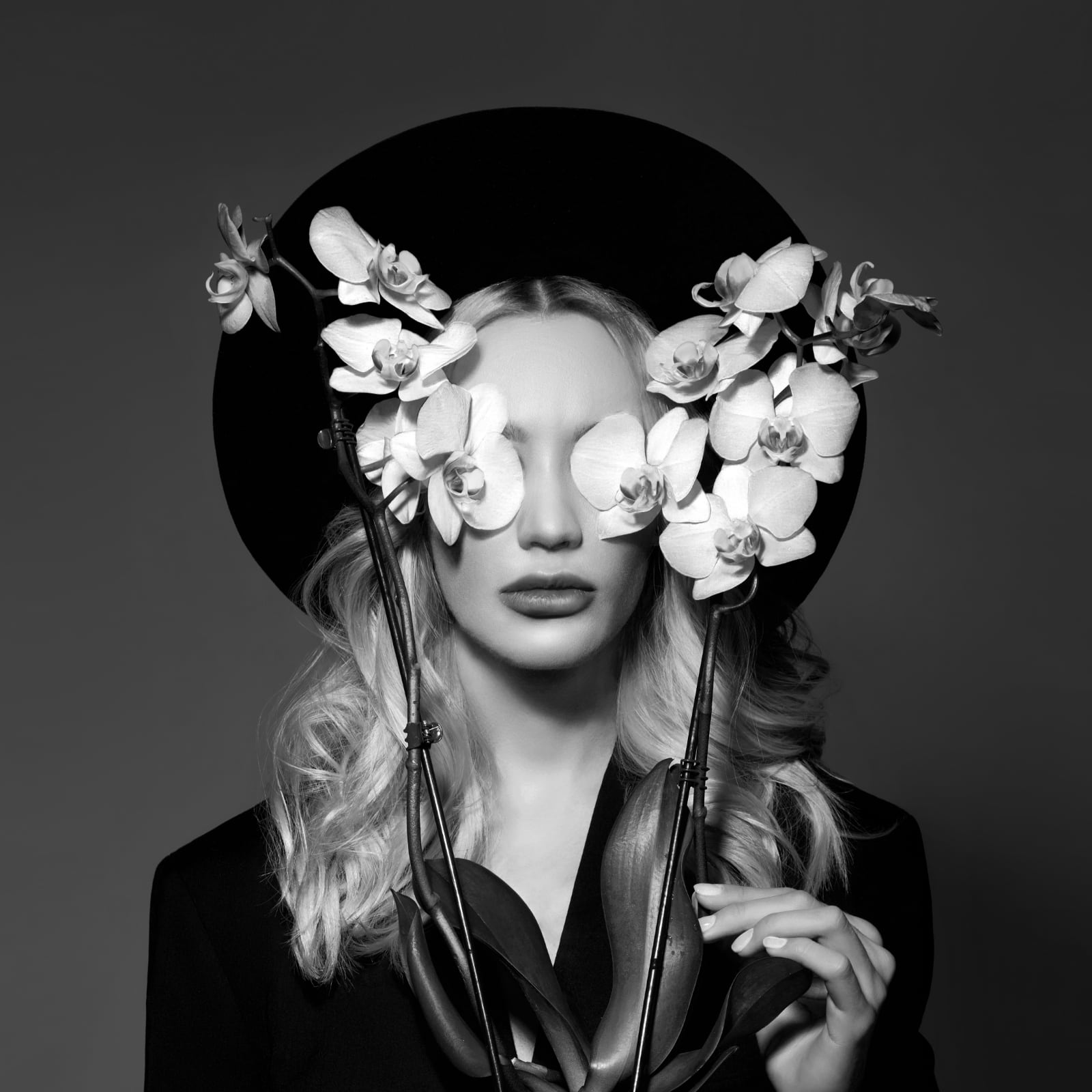 portret in zwart-wit van jonge blonde vrouw met hoed en twee orchidee's voor haar ogen