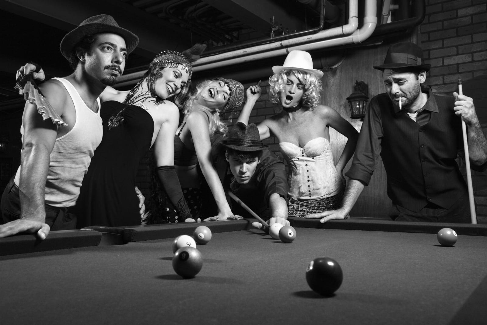 Drie dames en drie heren bij biljarttafel in ouderwetse zwart-wit kleuren