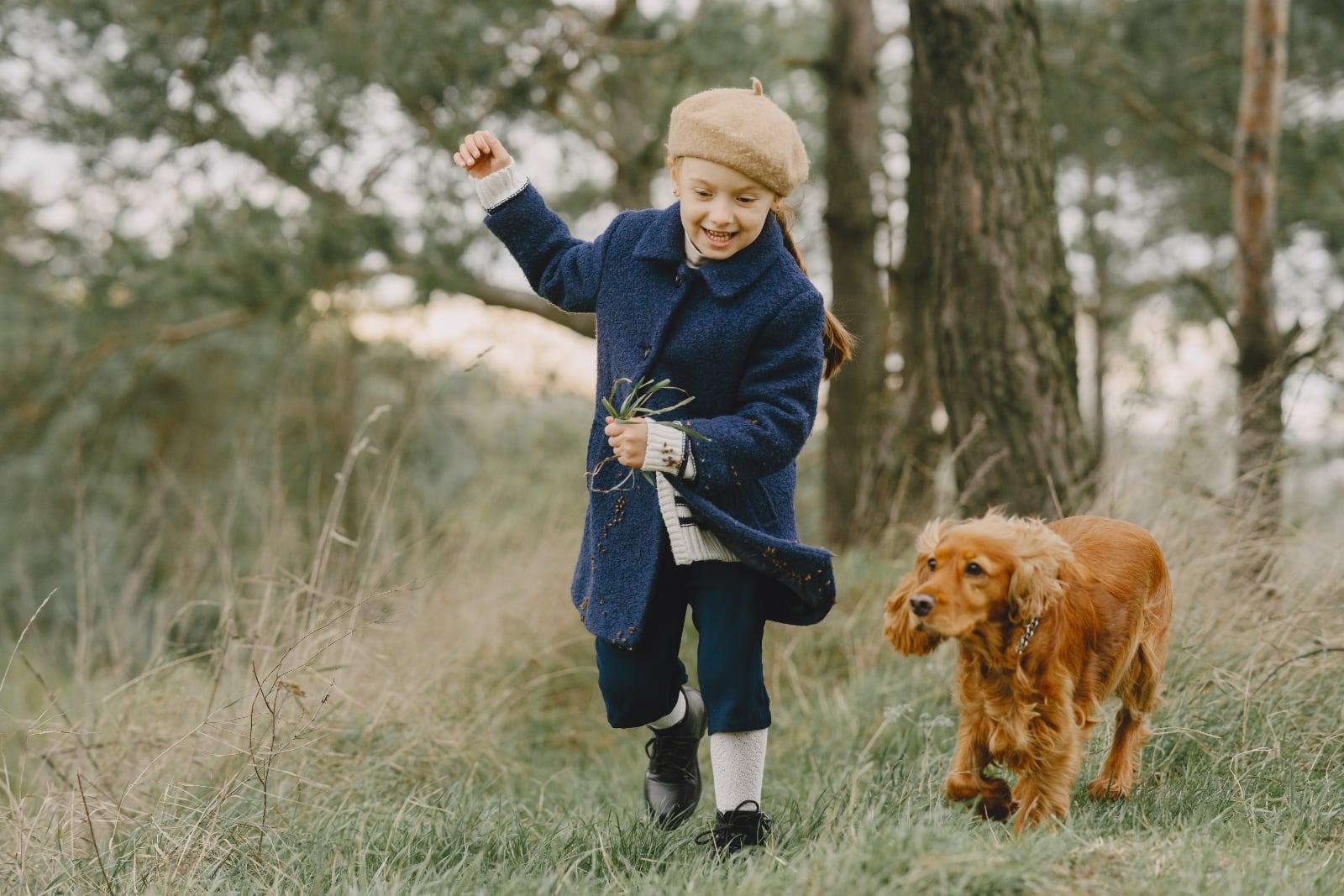 meisje met blauwe winterjas rent vrolijkmet hond in bos