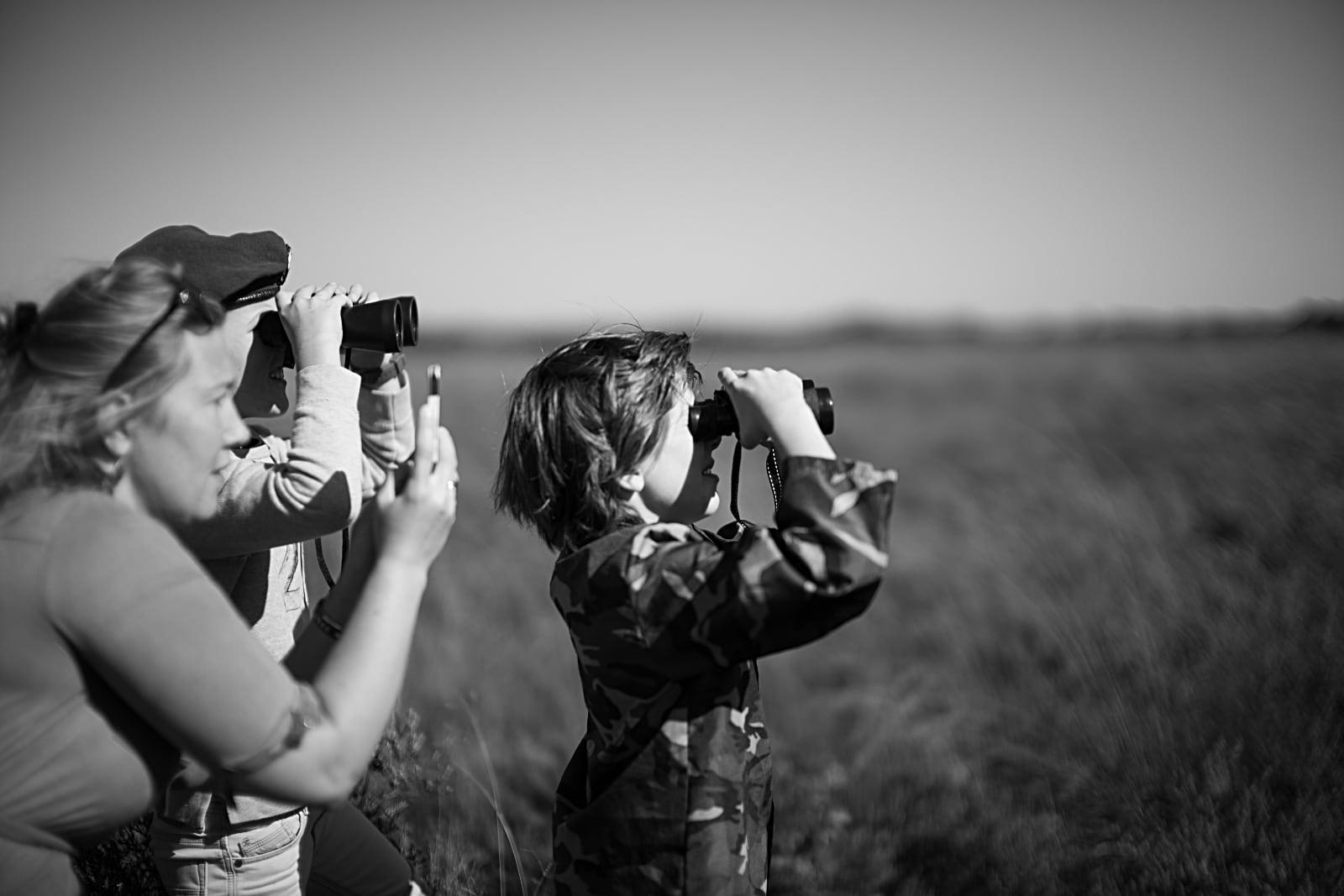 75 Jaar Vrijheid in Beeld - © Sacha de Boer - Airborne luchtlandingen herdenking op Ginkelse Heide, vrouw maakt foto's met mobiel en man en kind met verrekijker
