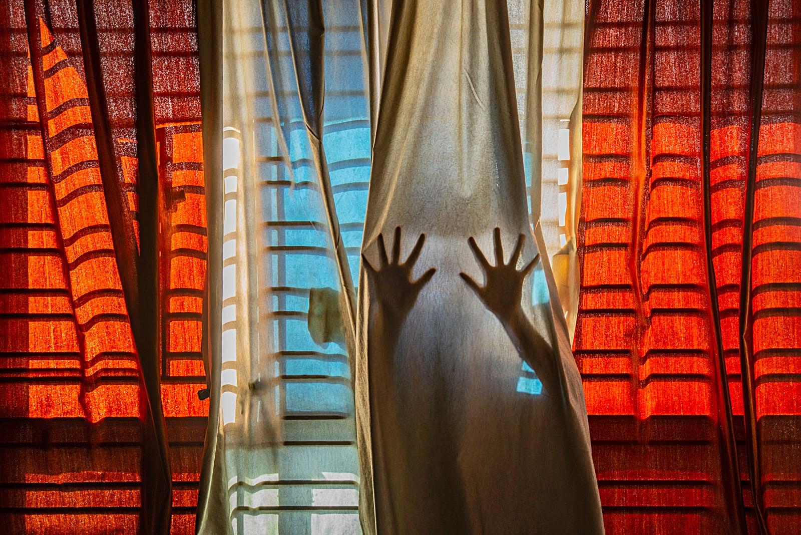 foto: © Pubarun Basu, India, Shortlist, Youth, Composition and Design, 2021 Sony World Photography Awards - Van achter de gordijnen probeert een paar handen door te breken,