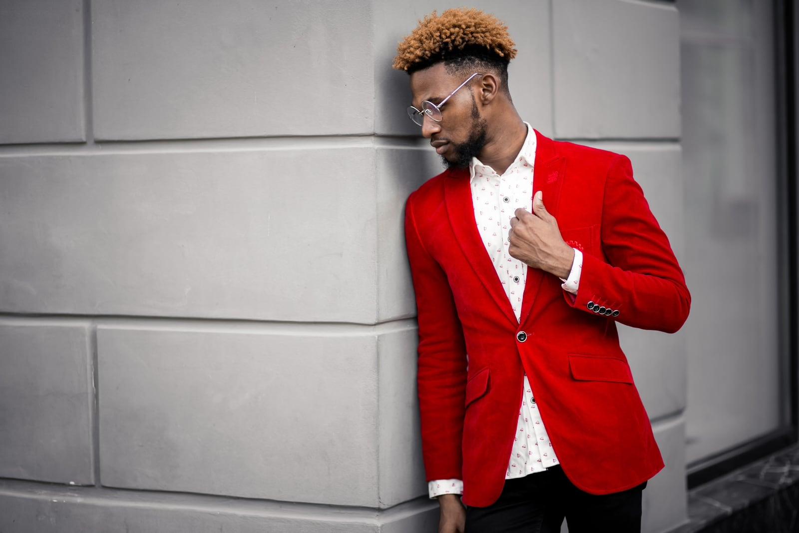 Voorbeeldfoto voor fotowedstrijd ROOD op Fotografie.nl, een man met rood colbert leunt tegen een mooie muur