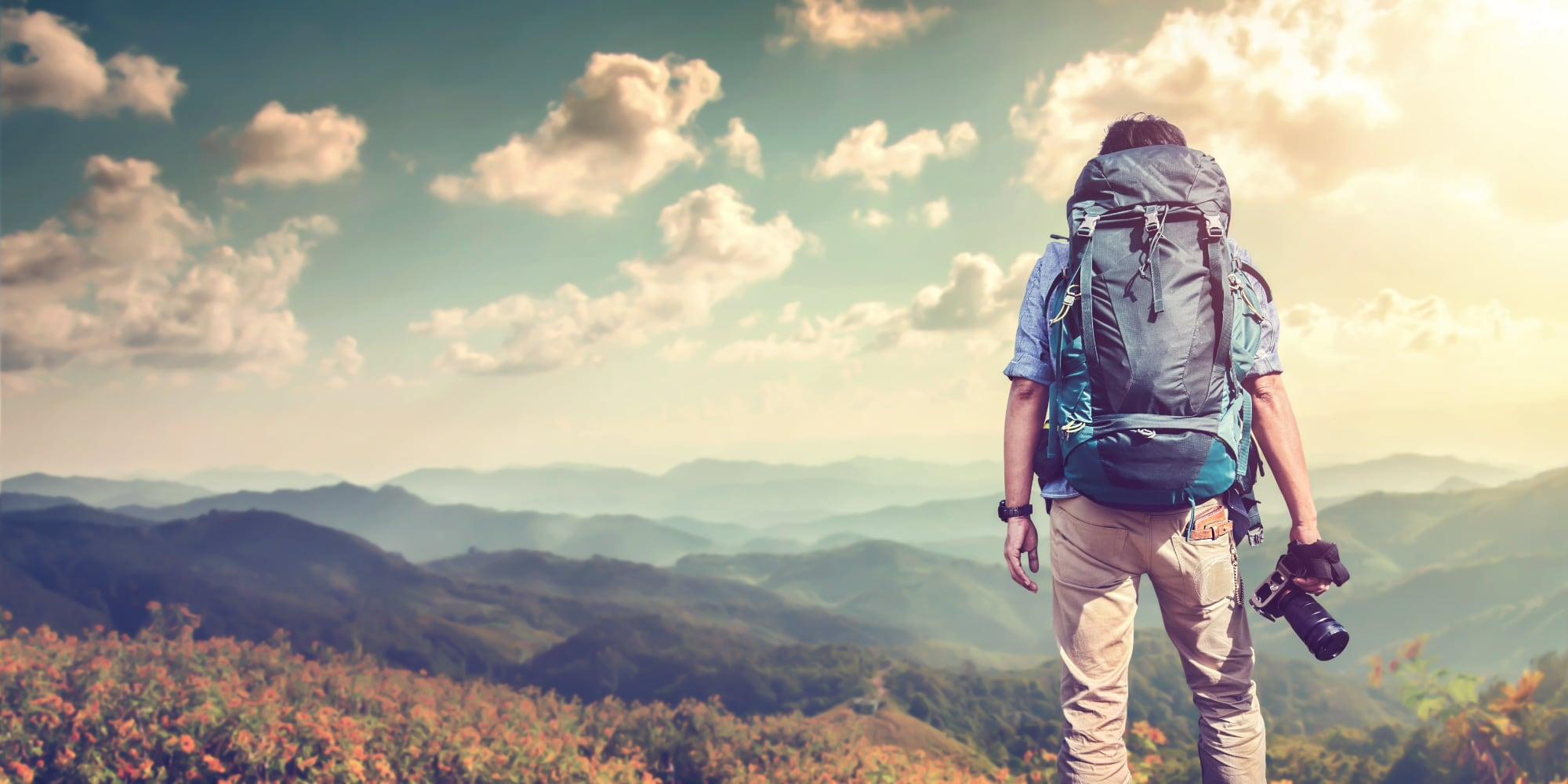 jonge fotograaf met camera in hand op bergen vanaf zijn rug gezien