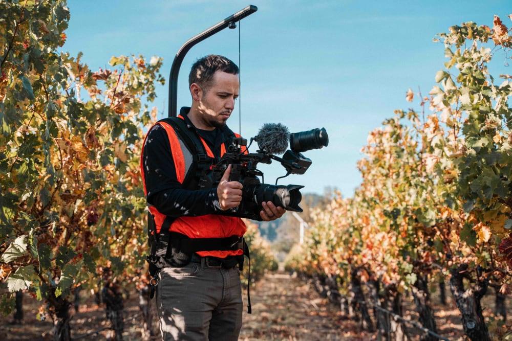 videograaf buiten in boomgaard aan het filmen