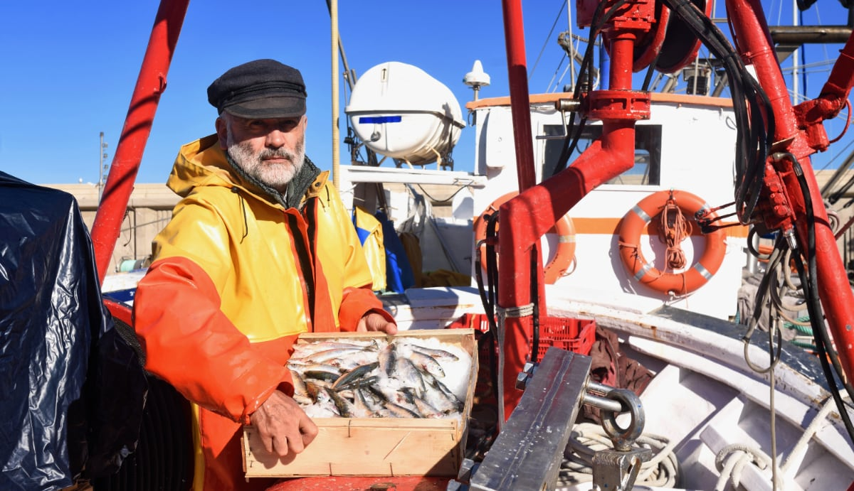 portret van visser p zijn boot in de zon