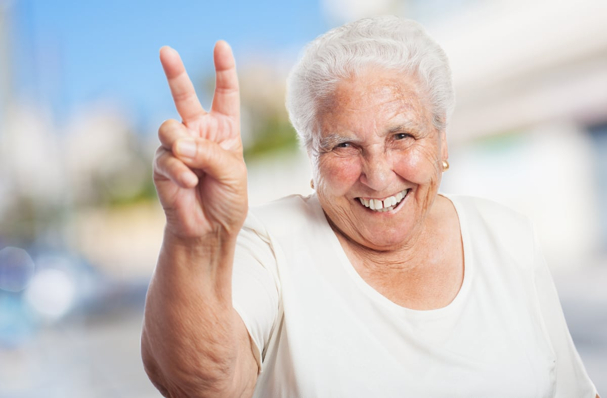 grandmother-with-two-fingers-raised-smiling