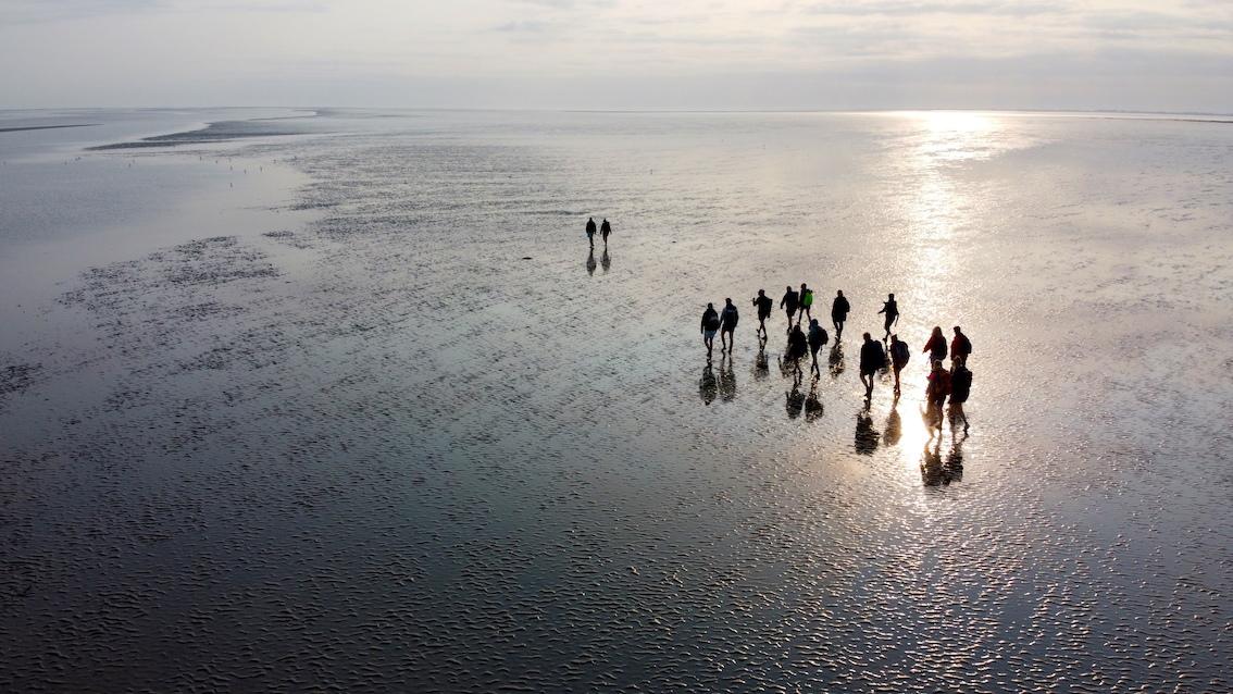 groepje fotografen van bovenaf gefotografeerd op wadden tijdens workshop bij ondergaande zon