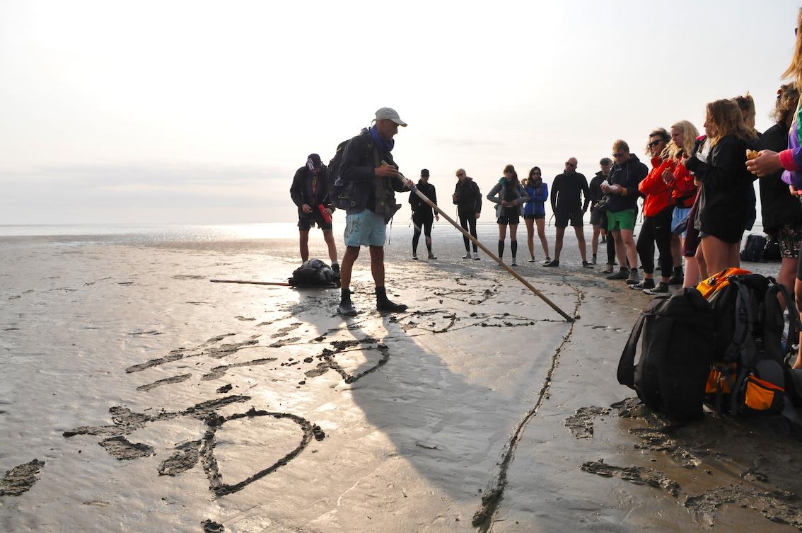 wadloop fotografie workshop op wadden met fotograaf Tom van der Leij - uitleg aan groep op het natte zand