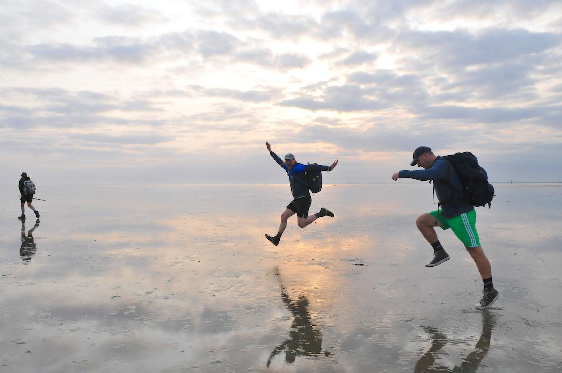 In de lucht springende fotografen op wadden tijdens fotografie workshop door Tom van der Leij