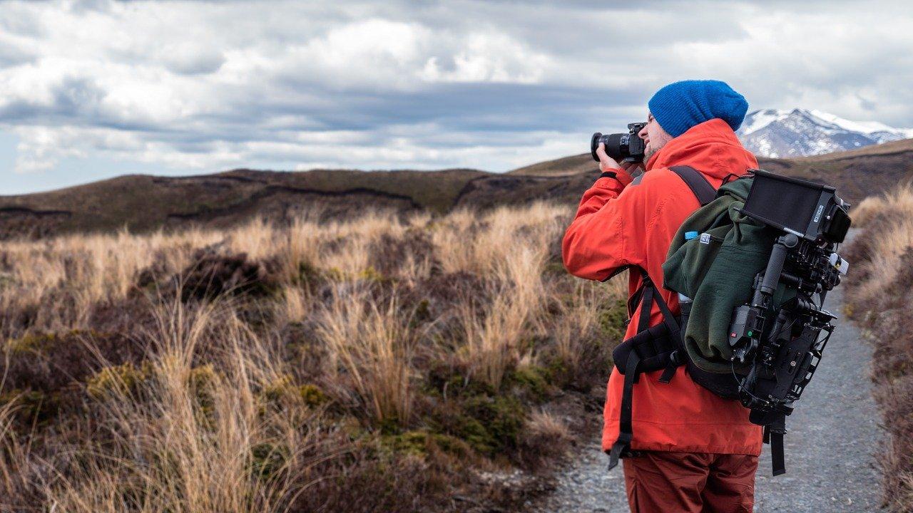 fotograaf met blauwe muts in landschap met bergen met camera voor gezicht en met rugzak en camera op rug