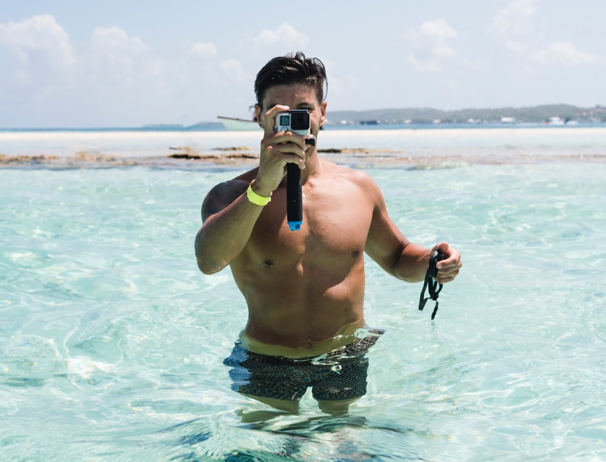 man staat in zee met GoPro in hand