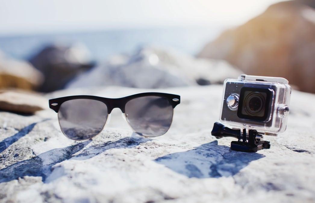 zonnebril en GoPro op rots met uitzicht op zee