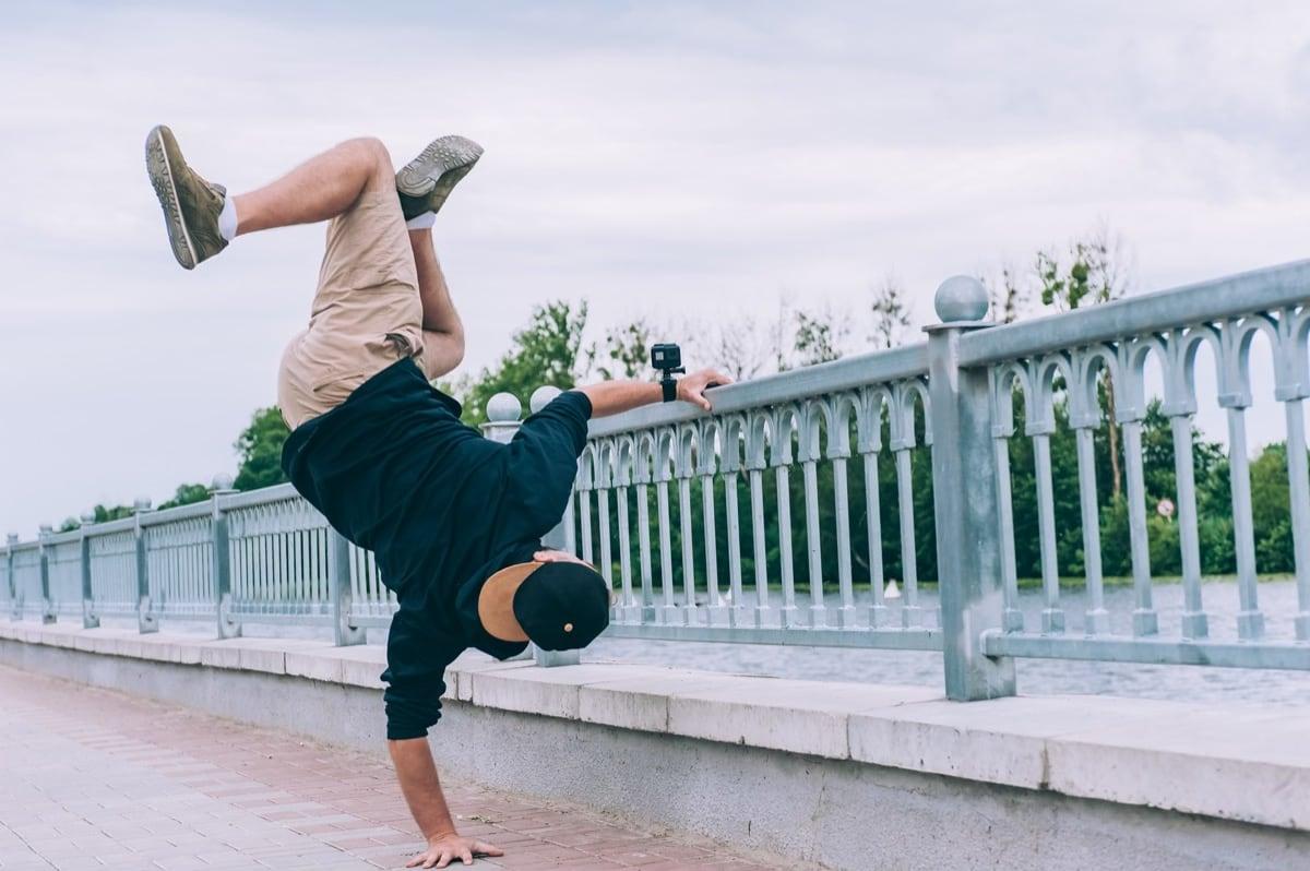 man doet breakdance bij brug met GoPro aan arm