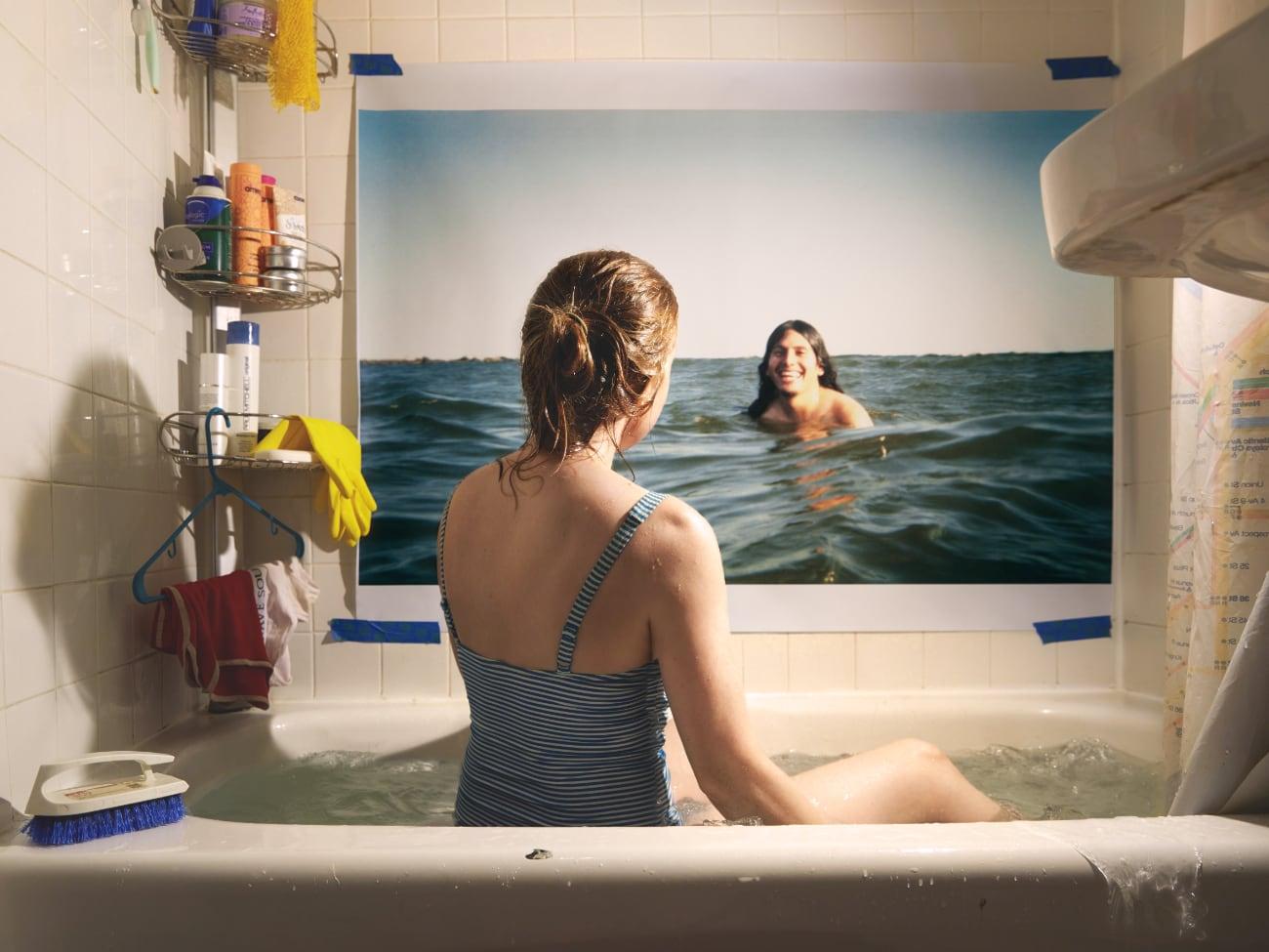 foto: © Alison Luntz - In Spirit - That Sunny Day: vrouw zit in bad en kijkt naar foto van vrouw die in zee zwemt