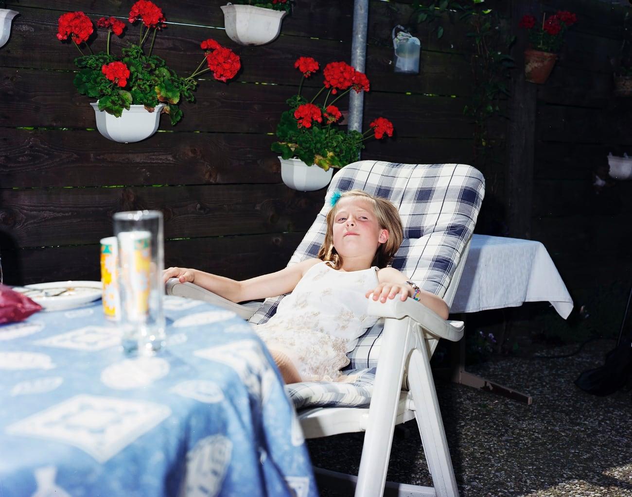 meisje in tuinstoel in tuin uit Thuis in de stad expositie van Raymond Wouda