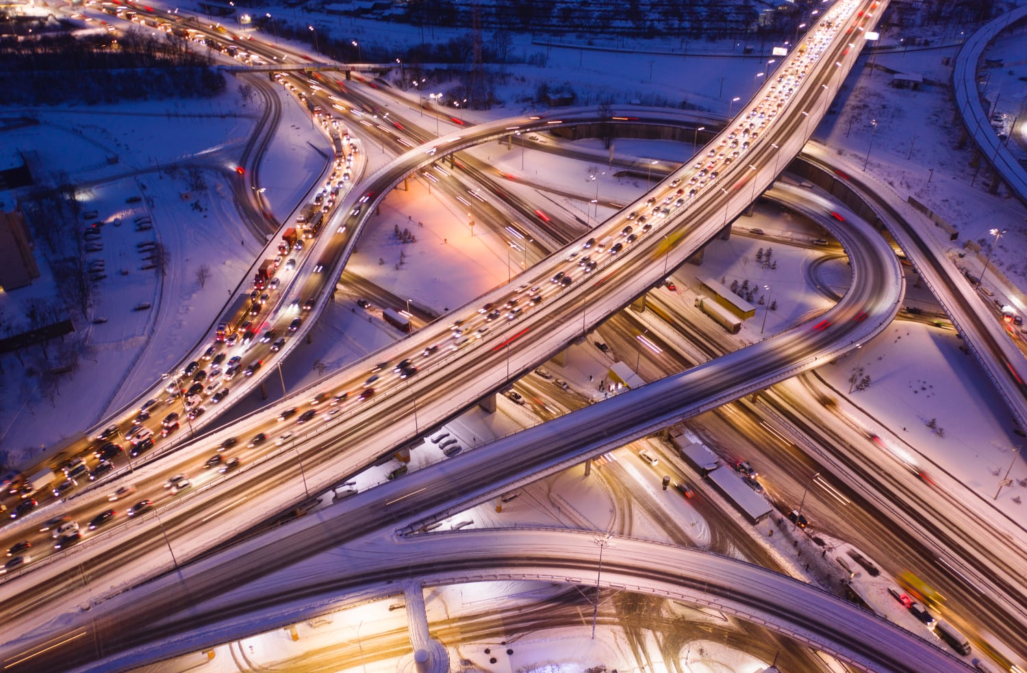 multi-level-complex-transport-interchange-loaded-with-traffic-winter-evening-road-is-illuminated-by-lanterns-drone-view
