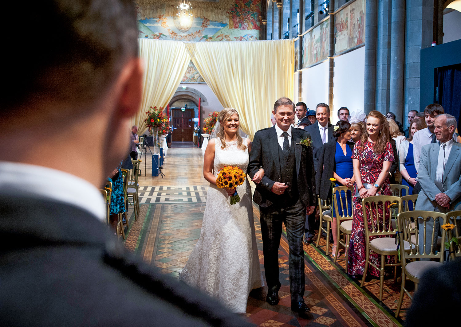 I was just standing behind the groom as the bride walked down the aisle to capture her big smile and the happiness as she approached her groom, best spot for the photographer during the wedding ceremony