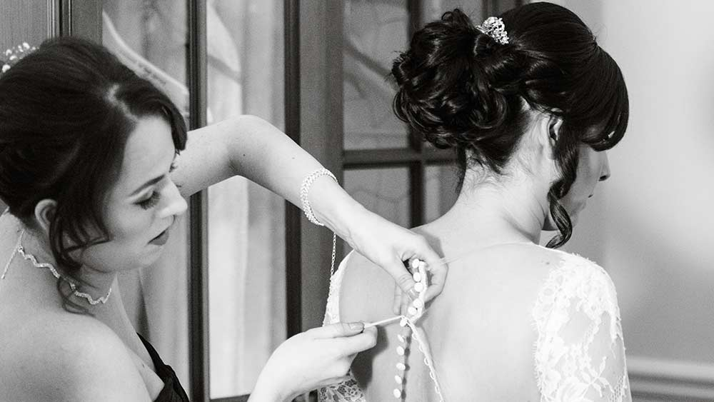 The bridesmaid is helping the bride into her dress with a crochet hook, which is super efficient for these style of buttons, bridal survival kit