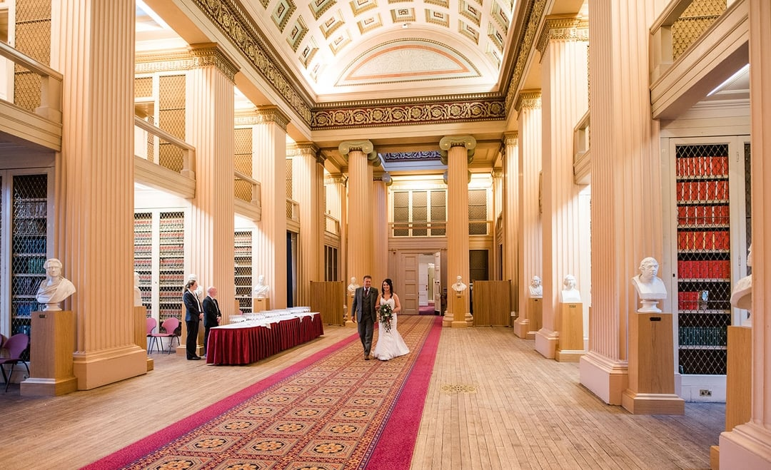 The bride and her dad, walking down the long aisle in the library, Playfair Library Wedding Venue Edinburgh