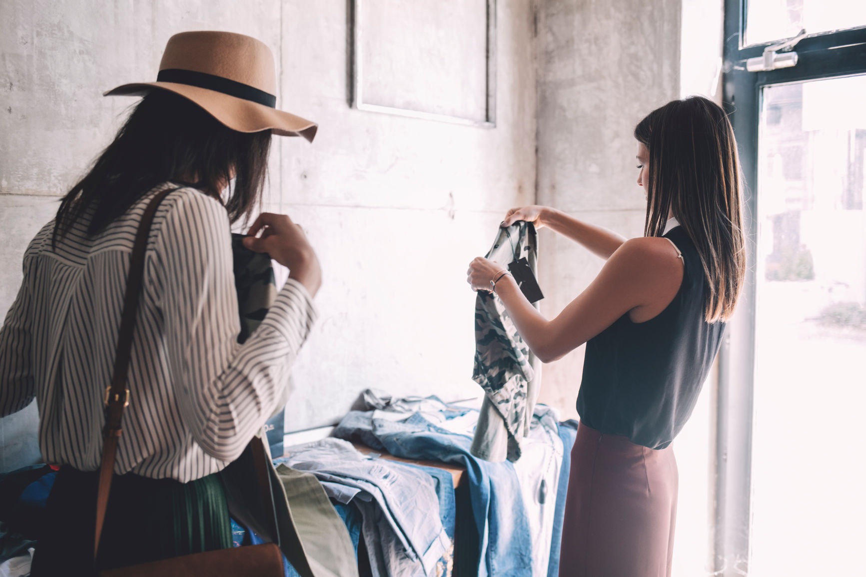 A store associate and a client shopping in a denim store | PredictSpring