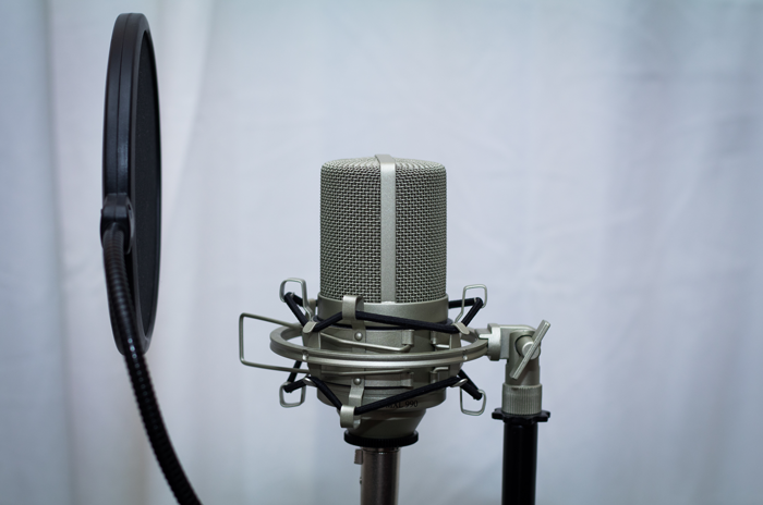 An image of a pop filter positioned 6 inches away from a microphone.
