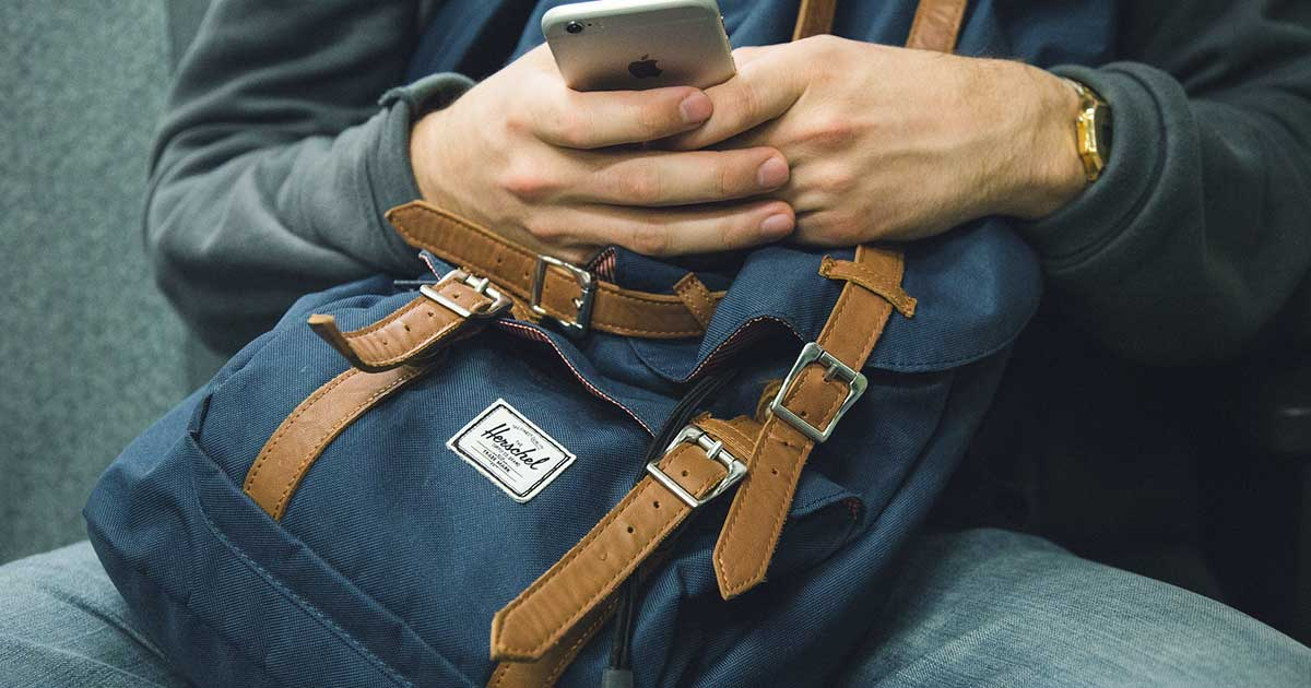 A person texting on a phone while holding a backpack.