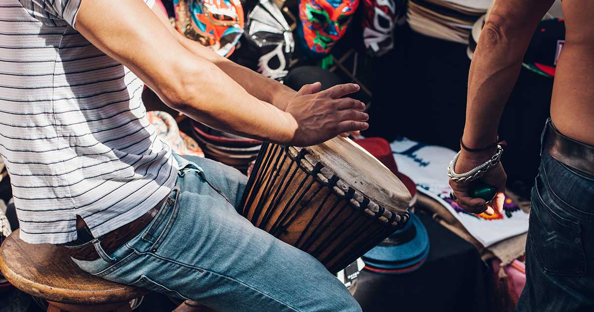 A person playing a hand drum.