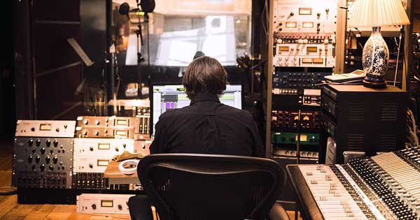 A music producer sitting in a studio.