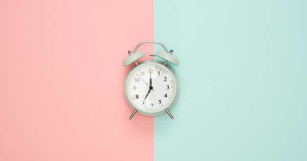 An alarm clock positioned in front of a pink and blue background.