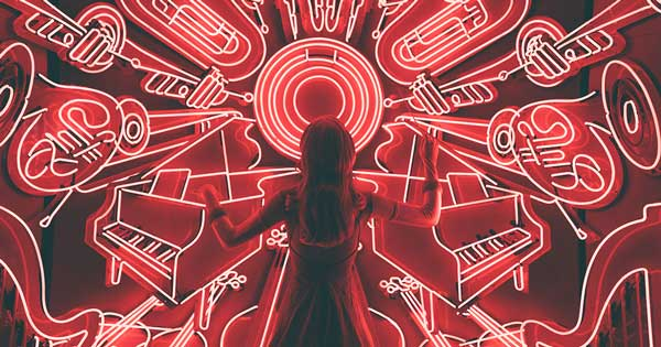 A woman standing in front of a wall of red fluorescent lights shaped like musical instruments.