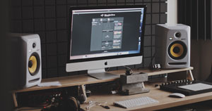 A computer screen and studio monitors placed on a desk.