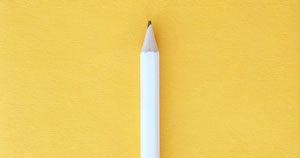 A white pencil with a yellow background.